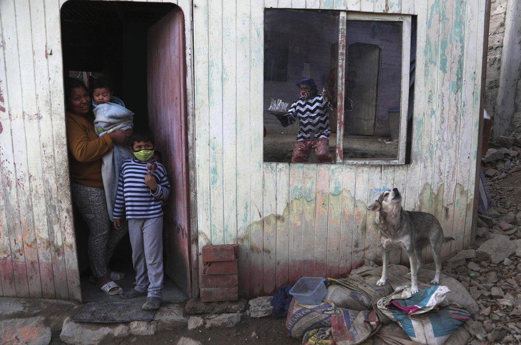 從窗戶反映出來的Jhona Zapata是為在秘魯馬戲團工作的小丑。疫情期間,馬...