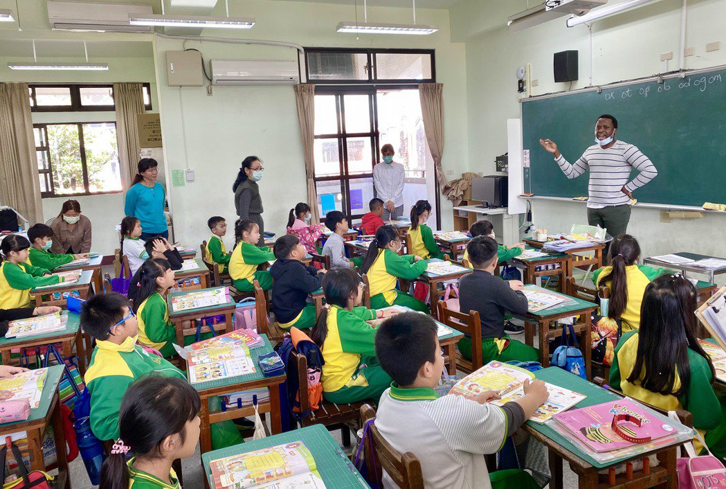 外籍教師一個口令一個動作,學生整齊劃一地唸出發音課本上的英文及單字。記者宋健生/...