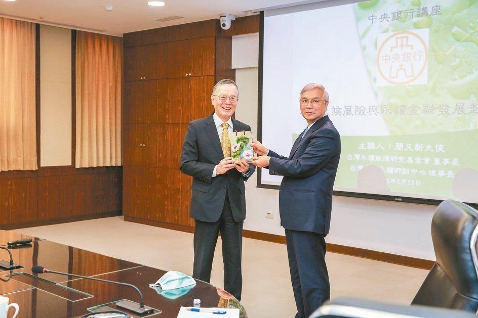 央行總裁楊金龍(右)致贈禮品給主講人簡又新。台灣永續能源研究基金會/提供