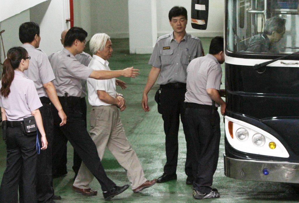 2010年,高院法官陳榮和(左二),由法警戒護戴著手銬,步上警備車。  圖/聯合報系資料照