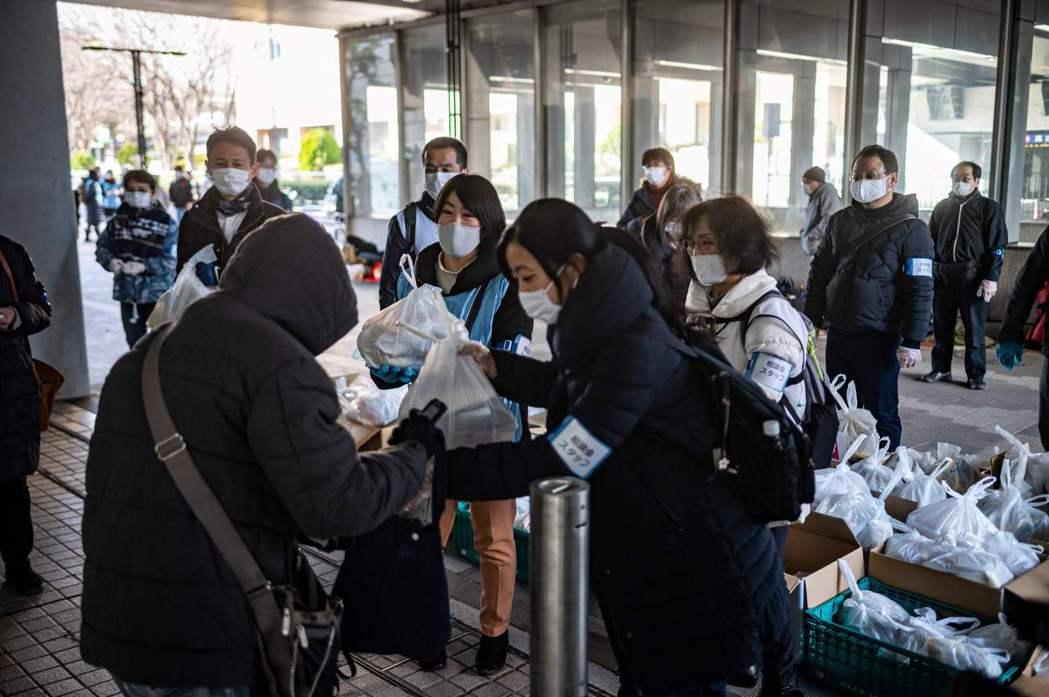 日本街頭愈來愈常見到因失業接受救濟的人群。法新社