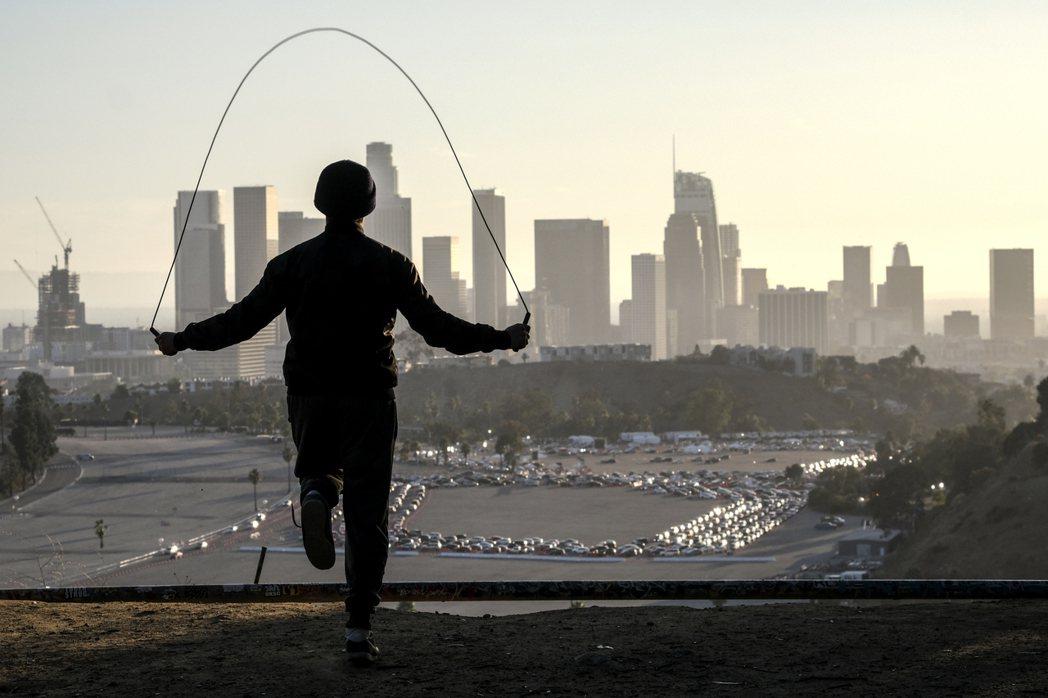 一名19歲少年在美國洛杉磯一處高地跳繩,看著遠方道奇體育場大批駕駛人開車排隊等著...