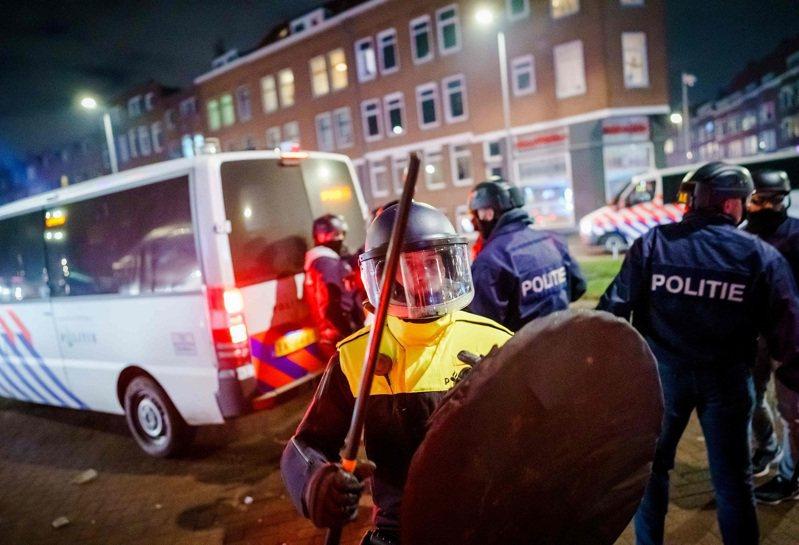 荷蘭23日發布新冠宵禁令,引發全國連續3晚非法抗爭與暴動,圖為鹿特丹警方25日晚間出動鎮暴。法新社