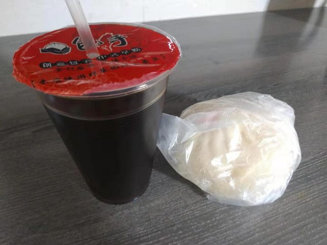 原PO在PTT貼在隔離首日吃到的早餐,是一顆包子加一杯飲料。圖/翻攝自PTT
