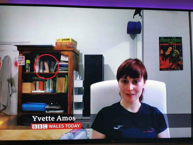 BBC今日威爾斯26日晚間採訪艾莫斯,請她分享新冠肺炎疫情期間的失業經歷,但眼尖的觀眾與網友都注意到,在她後方的書架上面,竟大喇喇地放著一個男性生殖器外型的性愛玩具。畫面翻攝:Twitter/GrantTucker