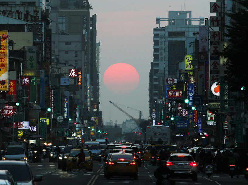 一年兩次高雄青年路「懸日」奇景登場,當夕陽落在青年路底時,在空氣中的懸浮微粒遮蔽到太陽,光線顯得微弱。記者劉學聖/攝影