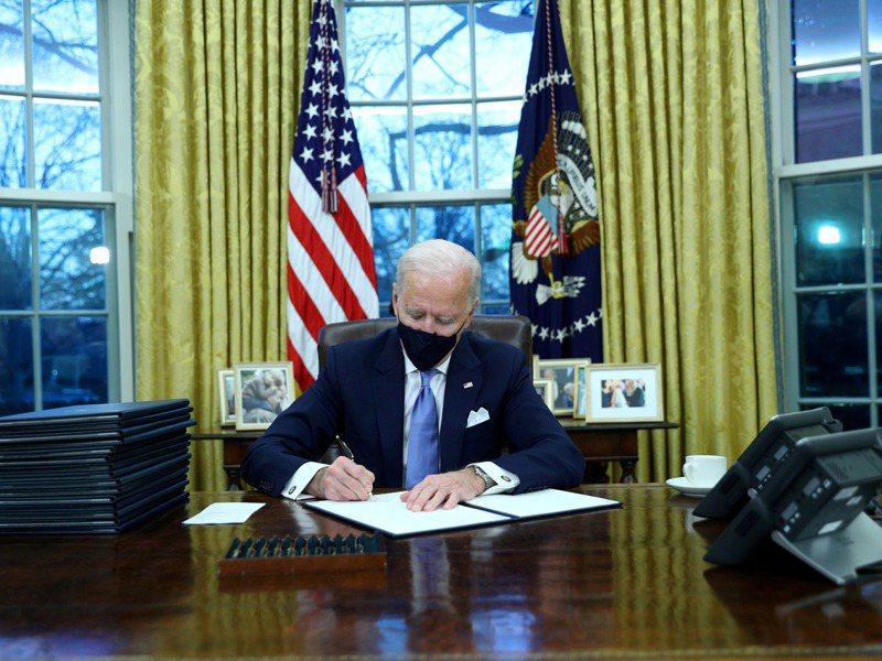 美國總統拜登20日就職當天戴著口罩在橢圓辦公室簽署行政命令。路透