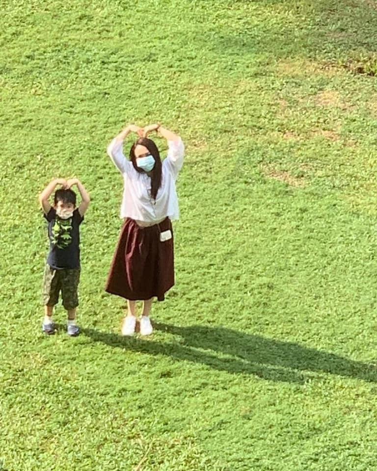 李銘順在隔離期間,范文芳帶著兒子到飯店外探望,妻兒同比愛心遙望,畫面超溫馨。圖/...