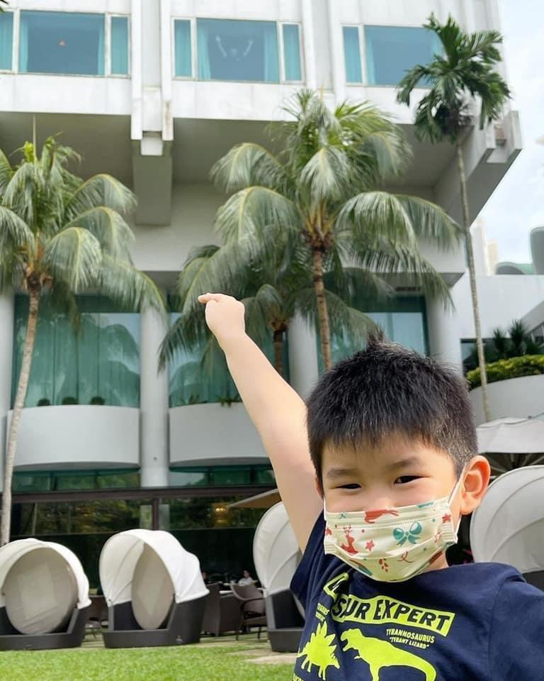 李銘順兒子指著飯店窗戶揮手的人,對鏡頭說「我的爸爸在這裡」。圖/摘自IG