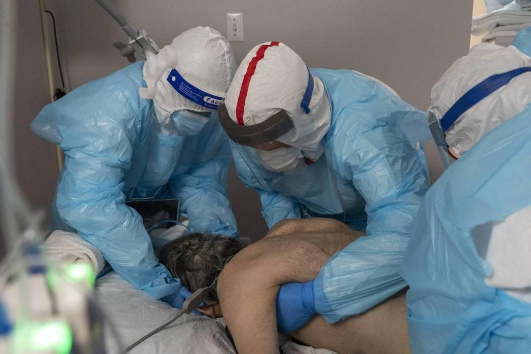 美國因新冠肺炎的死亡人數已超過二次大戰傷亡。圖為醫護在ICU為重症病人翻身。 G...