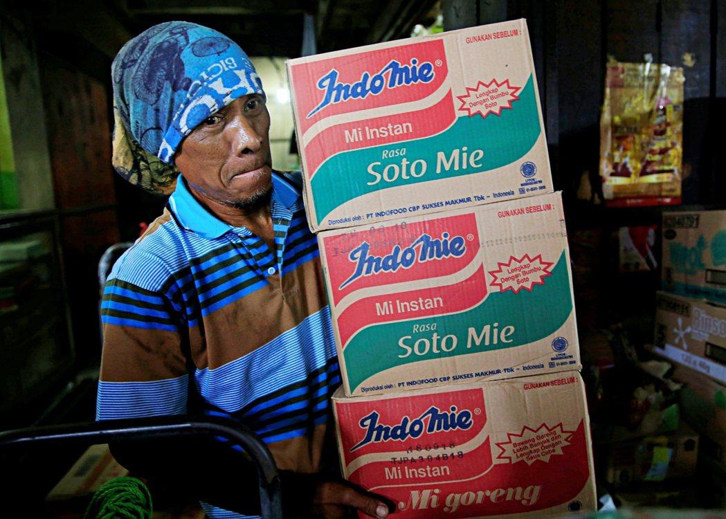 圖為2018年員工在印尼雅加達的市場拿著裝有營多麵的箱子。 圖/路透社