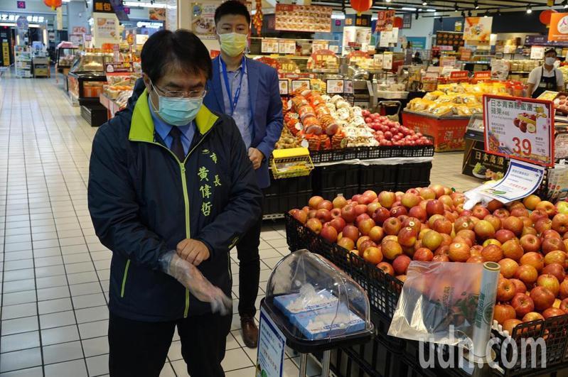 台南市長黃偉哲察看家樂福防疫,試用業者提供的拋棄式手套。記者周宗禎/攝影