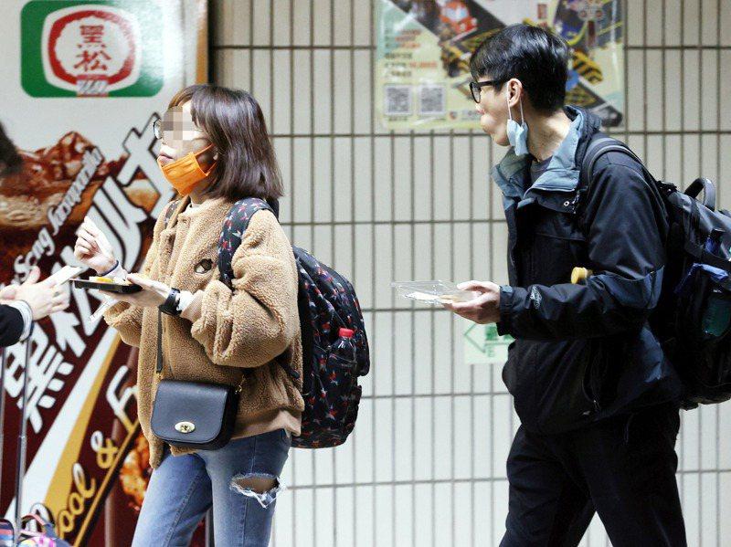 因應新冠肺炎疫情,台鐵宣布2月1日起車廂內禁止飲食,許多民眾在上車前,在月台上邊走邊吃,趕著解決手邊的食物。記者曾原信/攝影