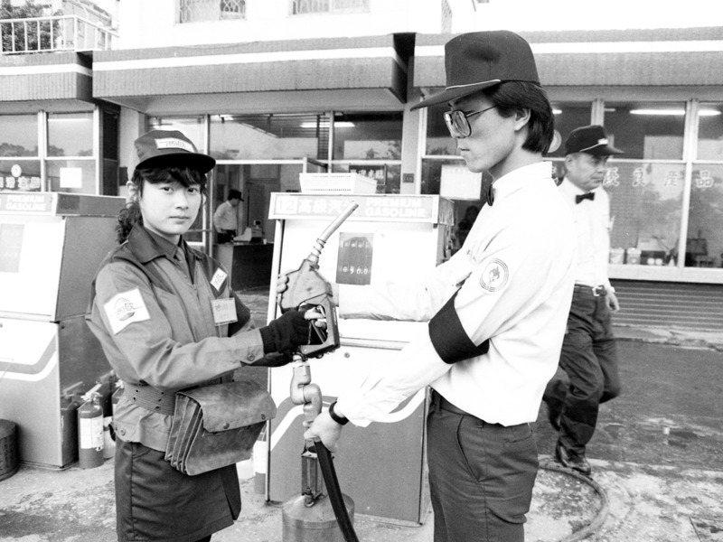 我國第一間民營加油站正式營業,西歐加油站人員(左)從中油人員(右)手中接過加油槍後正式開業。圖/聯合報系資料照片
