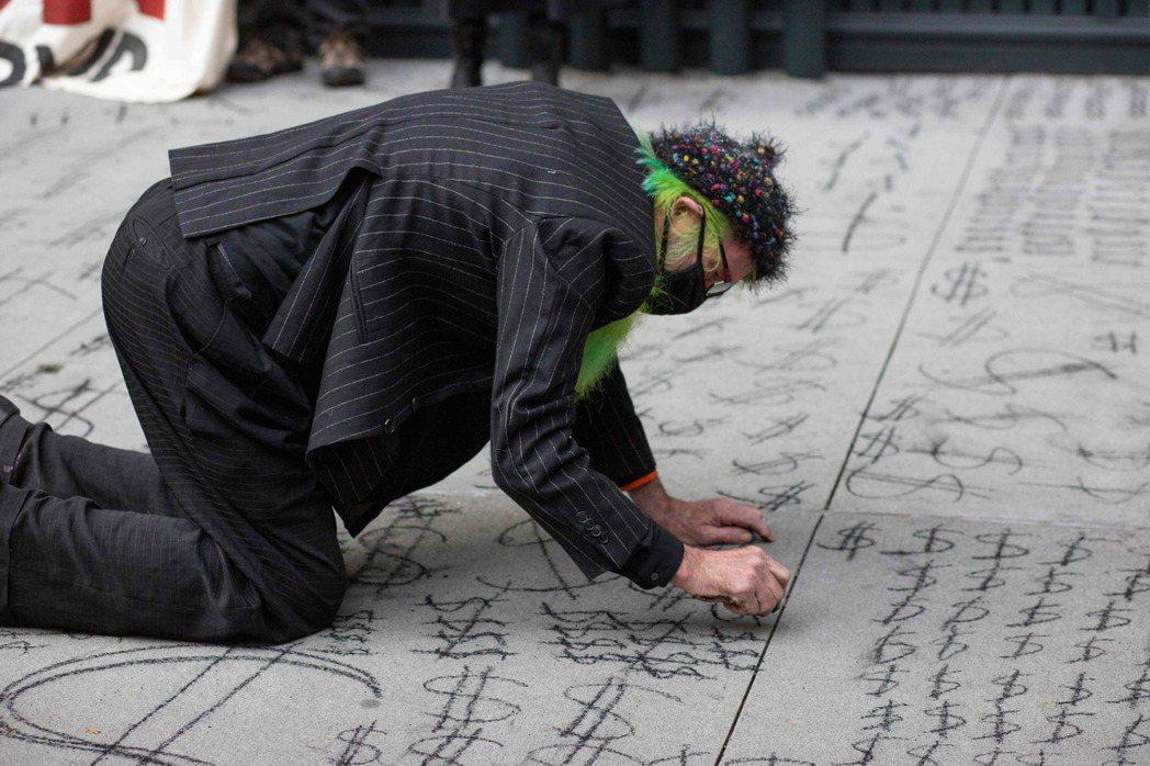 圖為2020年12月2日,亞馬遜的員工於紐約抗議示威,蹲低身體畫上錢的符號。 圖...