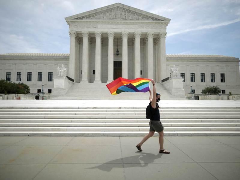 拜登政府正在籌設跨黨派總統委員會,研究美國最高法院及聯邦司法機關的改革。圖為2020年最高法院判決確定法律保障LGBT不被歧視的工作權後,一名男子在最高法院前揮舞象徵LGBT團體的彩色旗幟。法新社