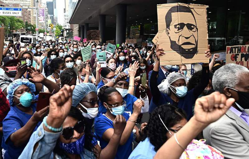 美國非裔男子佛洛伊德之死引爆全美抗議浪潮,眾議院今天通過禁止鎖喉和反對種族偏見的警察改革法案,圖為紐約民眾高舉佛洛伊德畫像抗議。法新社