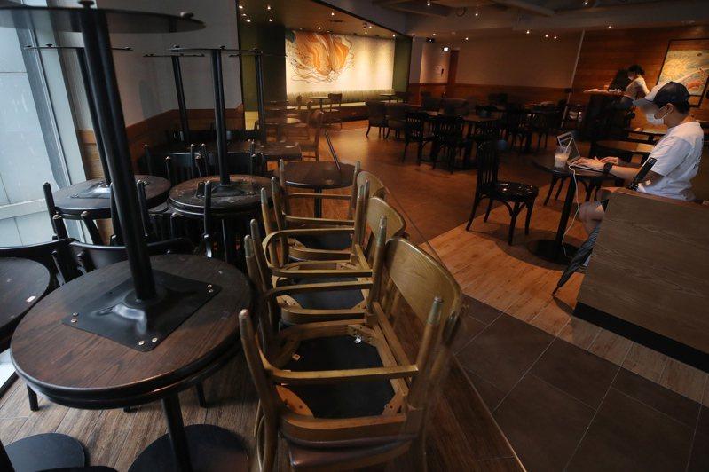 台灣許多店家自主停止營業,或限制室內消費人數。示意圖。圖為南韓首爾餐廳一家咖啡店配合防疫,收起內用桌椅。歐新社