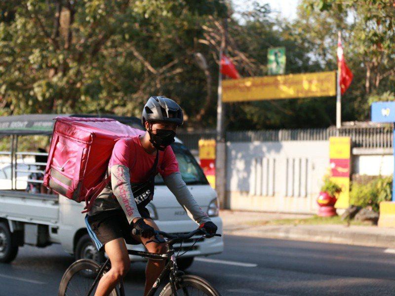 緬甸各地雖有零星抗議,但日常生活大致如常,一名外送員騎車經過國務資政翁山蘇姬故居門口。新華社