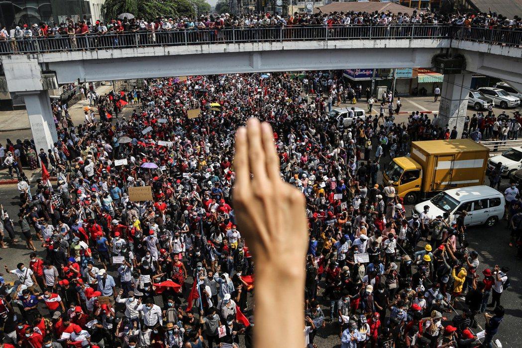 仰光大批民眾上街反政變,一名示威者比出三指手勢表示反抗軍政府。(路透)