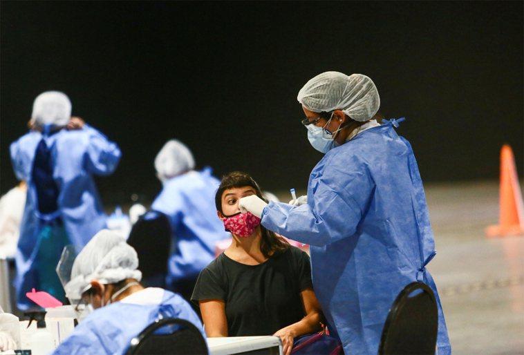 圖為醫療人員對民眾進行冠狀病毒疾病的測試。路透