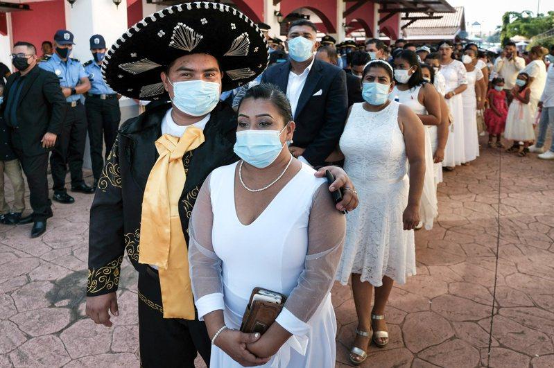 尼加拉瓜十四日在首都馬拿瓜舉辦情人節集團結婚活動,新人和賓客幾乎都戴上口罩。(路透)