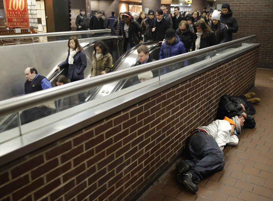 美國紐約兩名男子二○一五年三月在公車總站席地而睡。(美聯社)