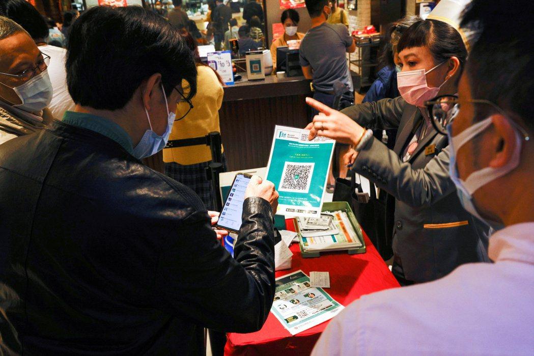 香港市民在進入食肆、戲院等場所前,都需出示手機上的「安心出行」追蹤程式,核實自己並非高危確診者。該程式變相等同強制全港市民,實名登記政府監控系統。 圖/路透社