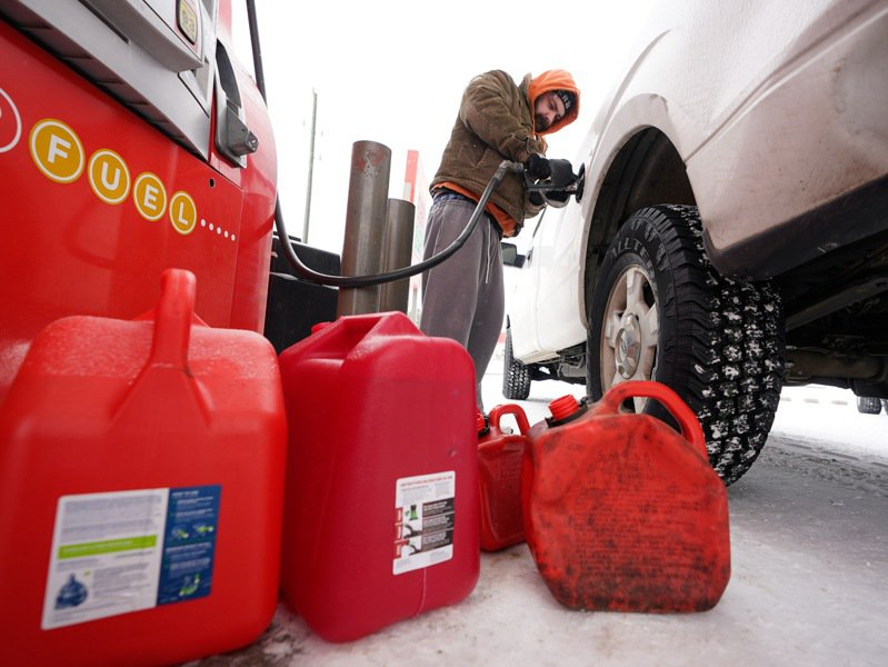 德州遭暴風雪侵襲,約有400萬民眾無電可用;圖為民眾忙著加油和買油。(美聯社)