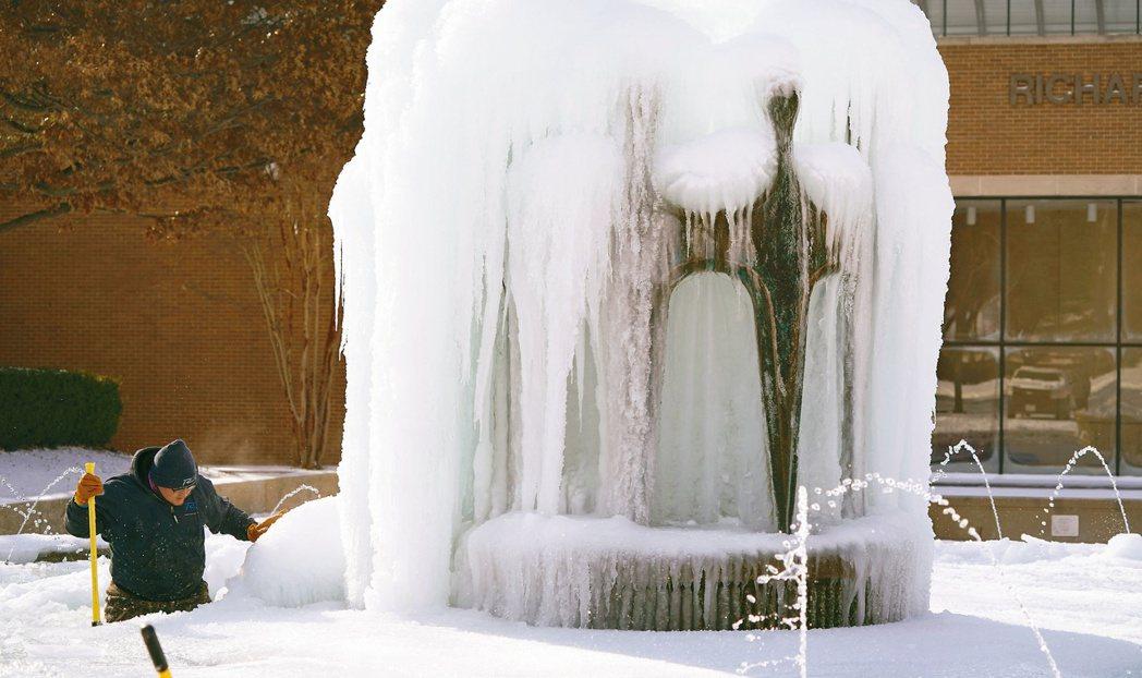 德州部分地區十六日出現攝氏零下廿五度低溫。圖為理察森市一名工作人員清理結冰的噴泉...