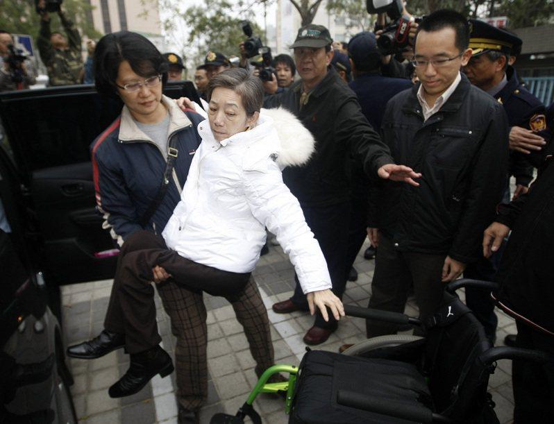 因龍潭案被判刑17年的吳淑珍,2011年02月18日到高雄地檢署報到,準備轉往台中培德醫院評估是否服刑,吳淑珍由看護抱起放在輪椅上,兒子陳致中(前右)在旁守護。圖/聯合報系資料照片