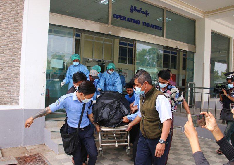 緬甸一名十九歲女子在九日警方鎮壓示威時遭實彈擊中頭部命危,家屬在十九日證實她不治身亡。醫院工作人員十九日將女子的遺體抬出醫院。(歐新社)