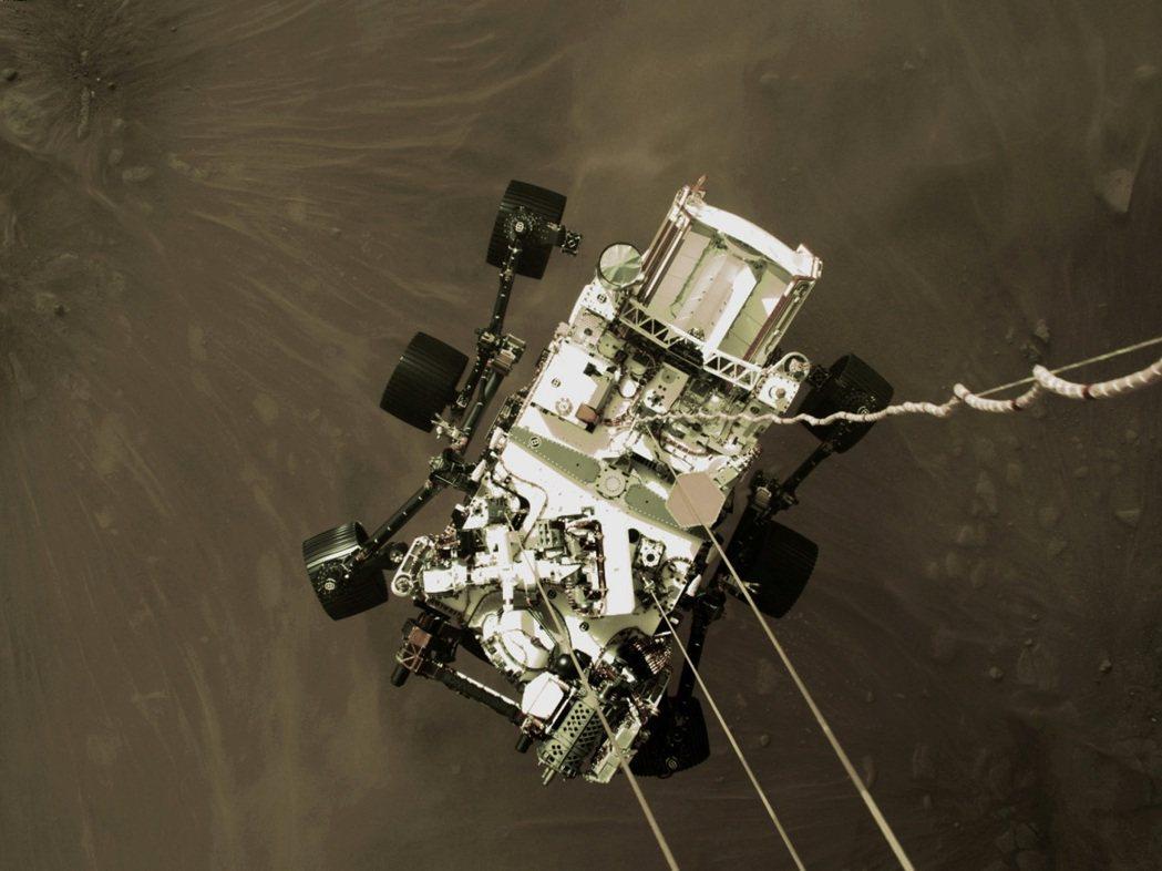 美國毅力號火星探測車18日平安著陸。距離地面僅約2公尺的「噴射背包」拍下「空中吊...