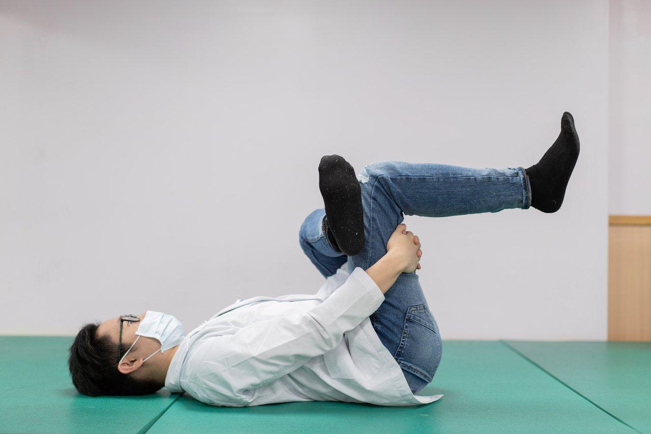 物理治療師施竣元示範臥鴿式放鬆運動,臥姿雙膝抱胸,並將左腳踝放在左大腿上方,雙手...