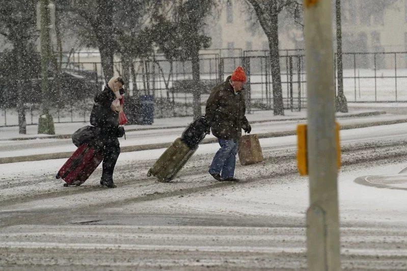 德州居民拖著行李在雪中行走。 圖/美聯社