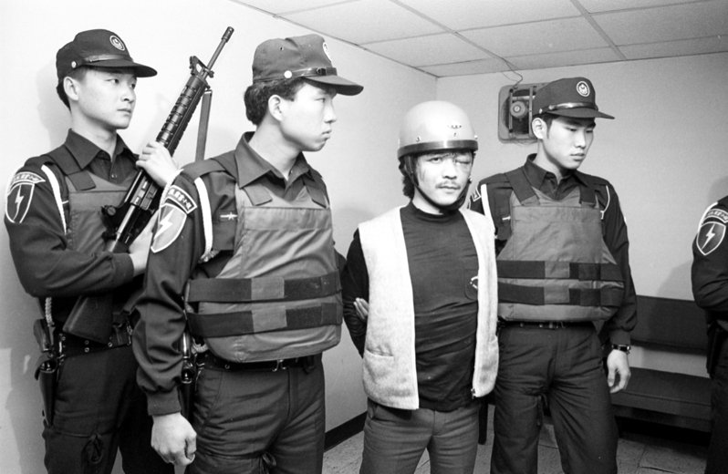 中華航空公司一架台北飛往高雄的國內線班機發生劫機事件,涉嫌劫機往大陸未遂的嫌犯簡渠淵(右2)被押回刑事警察局接受偵訊。圖/聯合報系資料照片