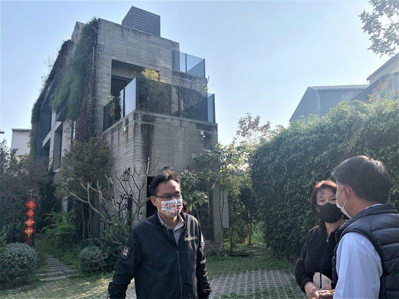 台中市議員張耀中指他身後這處民宅屋頂涉違規裝設基地台。圖/張耀中服務處提供