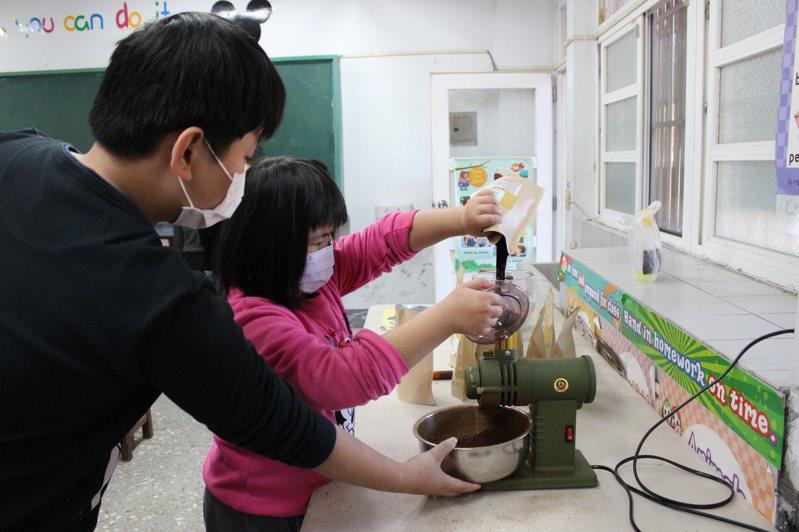 彰化芬園同安國小學生今天分工合作,學生磨豆製作咖啡掛耳包。記者林敬家/攝影