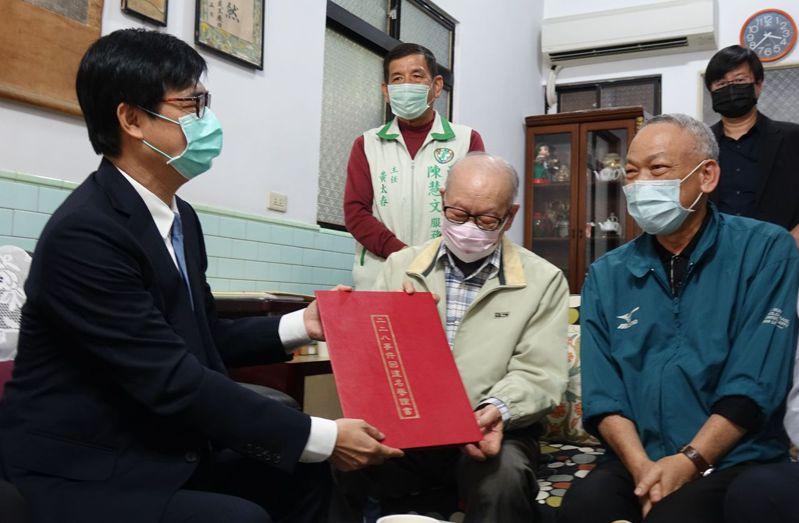 高雄市長陳其邁(前左)與228受難者蘇泰山家屬拿著蘇泰山的回復名譽證書合影。記者楊濡嘉/攝影