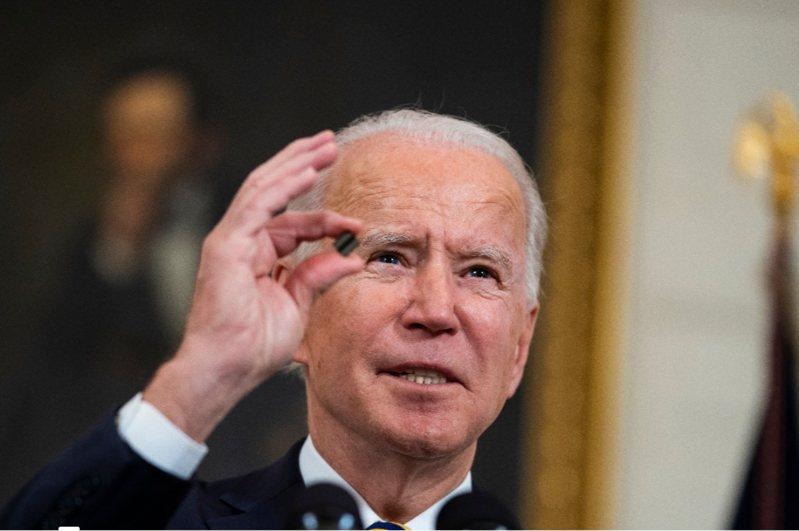 美國總統拜登用拇指和食指從講桌上捻起一小片電腦半導體晶片解釋,這個肉眼都不見得看得清楚的小晶片,拖延了汽車生產,減少美國勞工的工作時間。歐新社。
