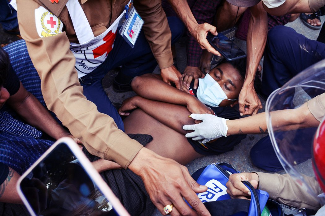 圖為2月20日緬甸中部大城曼德勒的示威行動,民眾被軍警射傷。 圖/路透社