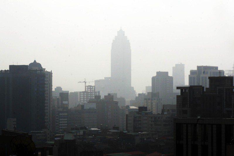 環保署25日表示,台灣北部、竹苗到中部空氣品質達紅色警示等級,提醒所有族群應減少在戶外活動,敏感族群應減少在戶外劇烈活動。圖為台北站前新光三越大樓幾乎隱沒在霧霾中。中央社