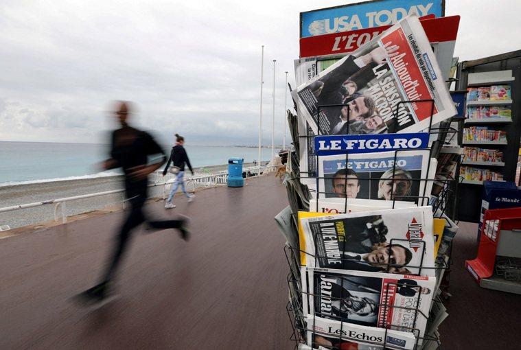 圖為法國尼斯一名男子路跑經過書報攤,攝於2017年。路透