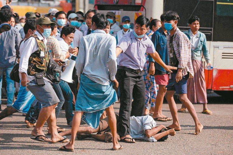 數名軍方支持者廿五日在仰光街頭圍毆一名男子,有人(左)持刀械。(法新社)