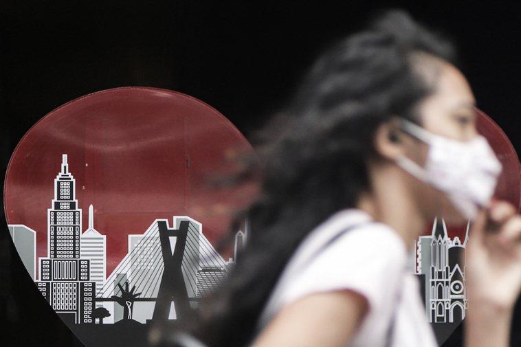 圖為一名女子戴口罩走在巴西聖保羅市街頭。新華社