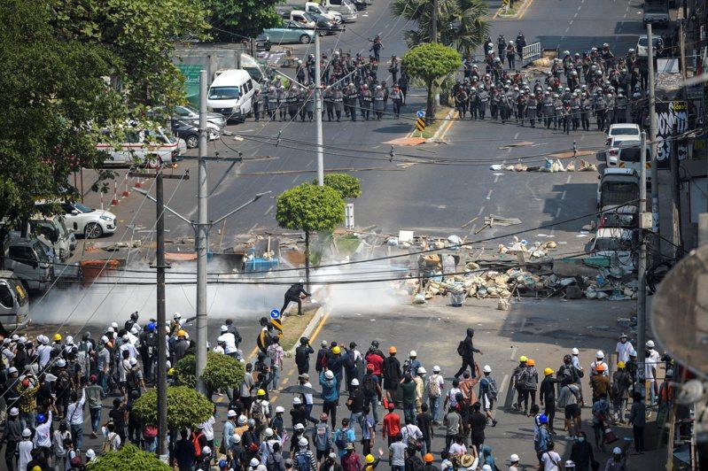 緬甸最大城仰光的反政變示威者二月廿八日隔著路障和鎮暴警察對峙。(路透)
