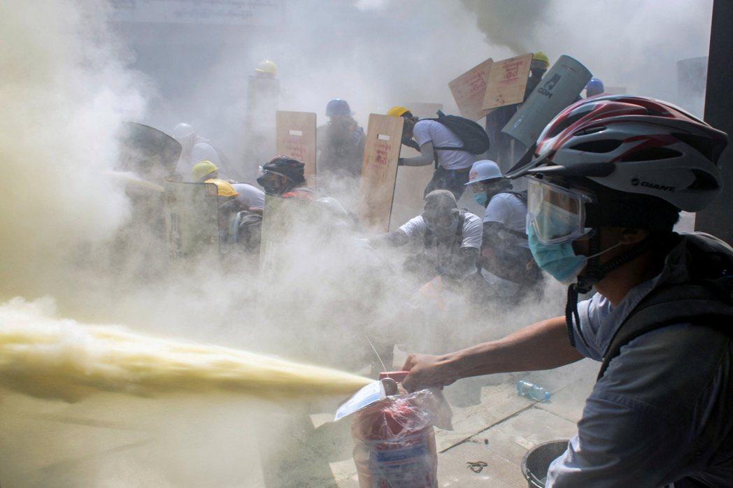仰光一名示威者拿滅火器朝鎮暴警察噴。(路透)