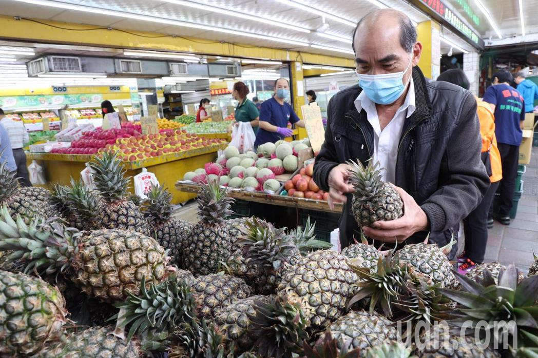 買鳳梨的民眾,仔細敲著一顆顆鳳梨,聽聲音選一顆好吃的。記者黃義書/攝影