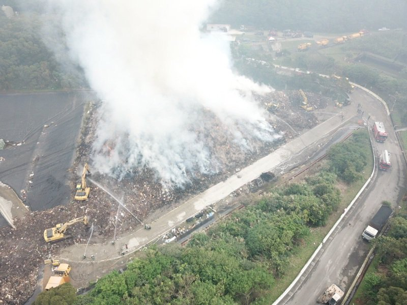 八里垃圾掩埋場火警到昨天仍持續延燒,消防局動用大批人力和消防車灌救。圖/新北消防局提供