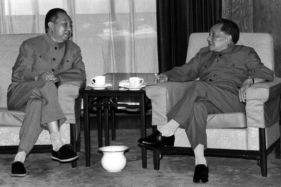 圖為1987年,鄧小平與華國鋒在出席全國人民代表大會全體會議期間在休息室交談。 圖/中新社